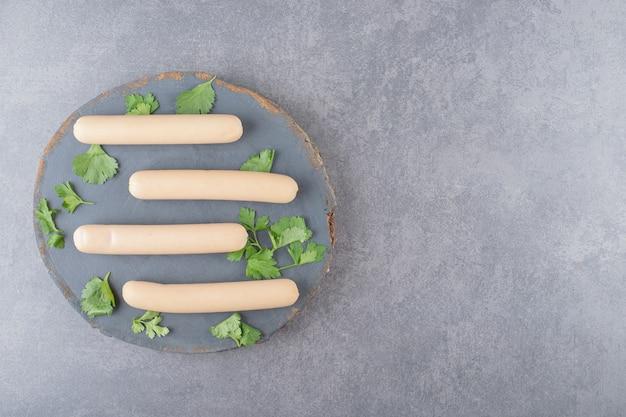 Een houten plaat met gekookte worst en peterselie