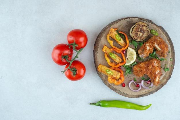 Een houten plaat met paprika's en tomaten op wit