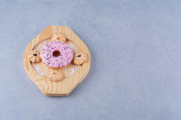 Een houten plaat van heerlijke roze donut met zoet koekje.
