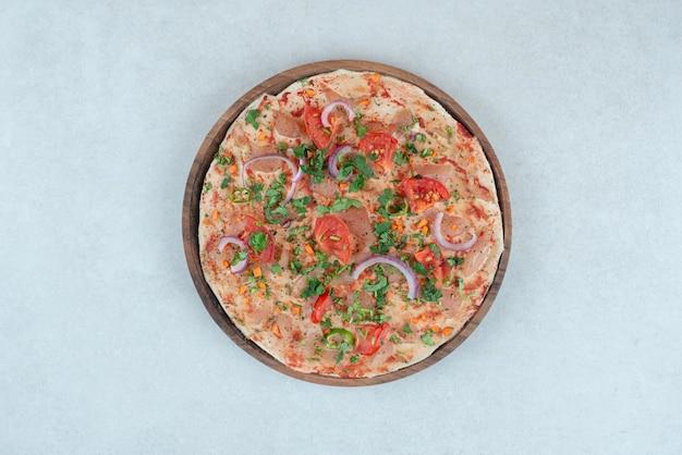 Een houten plaat van pitabroodje met gesneden tomaat en ui.