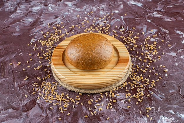 Een houten plaat van vers bruin broodje met zaden op lichte achtergrond.