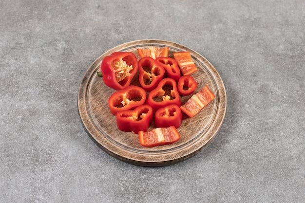 Een houten plaat vol gehakte rode paprika op een stenen oppervlak.