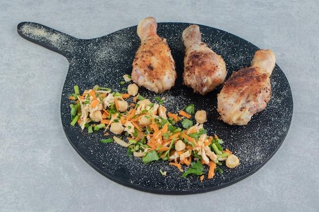 Een houten plank met gebakken kippenpoten en groentesalade.