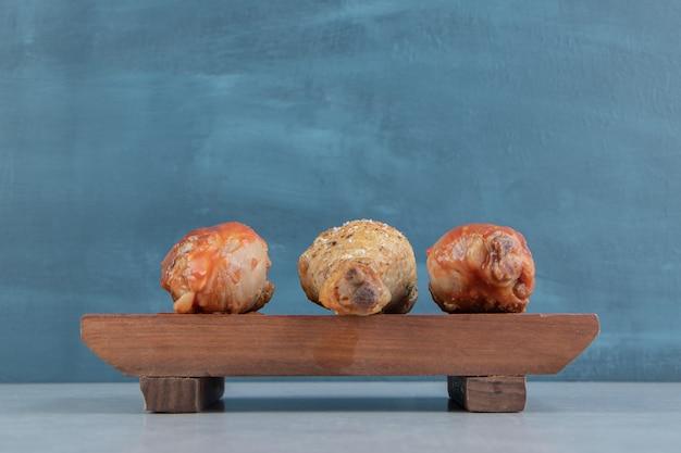 Een houten plank met gebakken kippenpoten vlees.