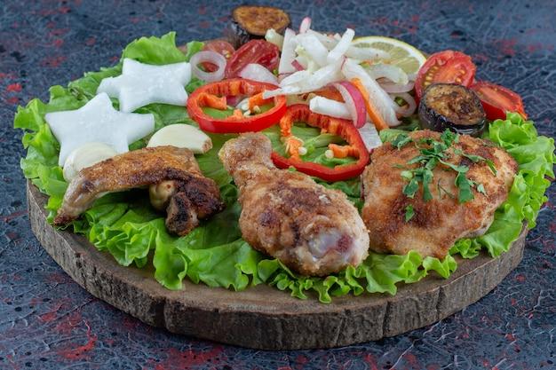 Een houten plank met gebakken kippenvlees en groenten.