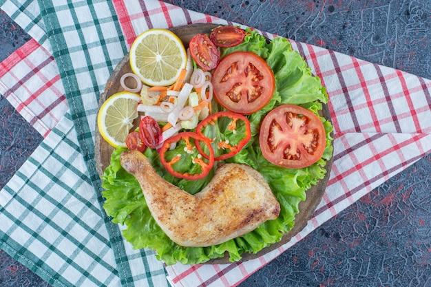 Een houten plank met gebakken kippenvlees en groenten