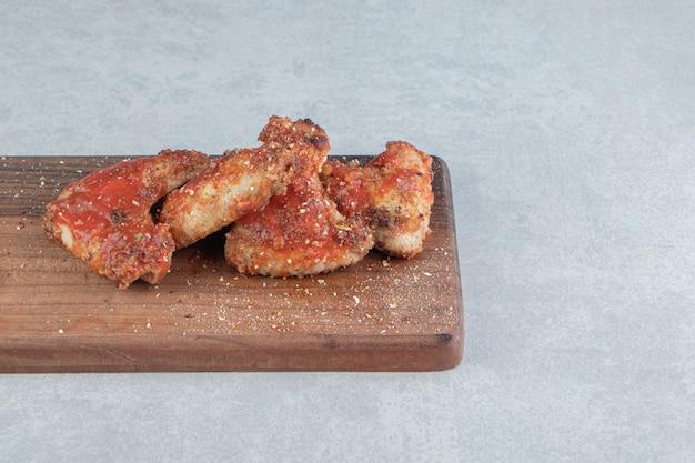 Een houten plank met gebakken kippenvlees met relish.