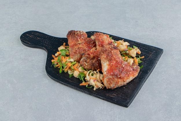 Een houten plank met gebakken vlees en groentesalade.