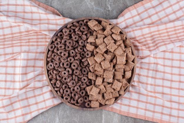 Een houten plank met gezonde chocoladegranenringen en cornflakes met chocoladepads.