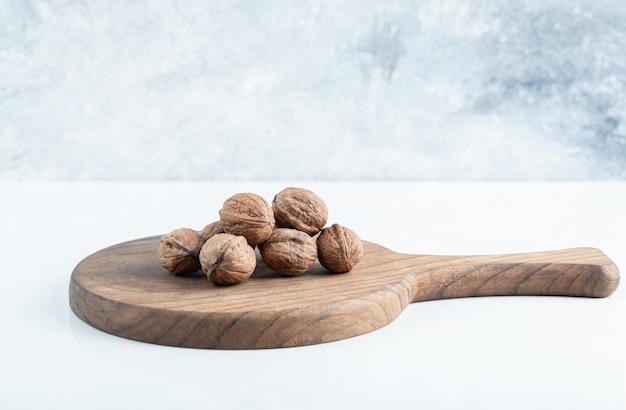 Een houten plank met gezonde walnoten op een witte achtergrond.