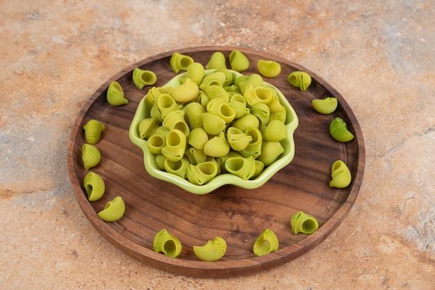 Een houten plank met groene onvoorbereide macaroni