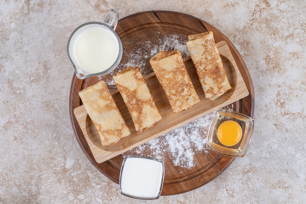 Een houten plank met heerlijke pannenkoeken en rauwe dooier
