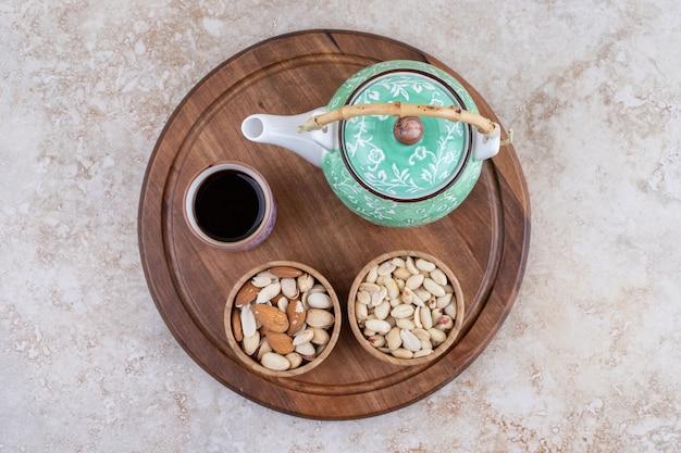 Een houten plank met theepot en noten