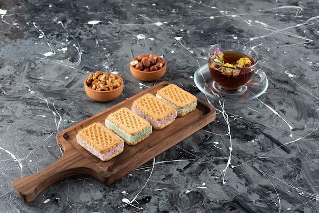 Een houten plank van belqian wafels met een kopje thee en gezonde nootjes.
