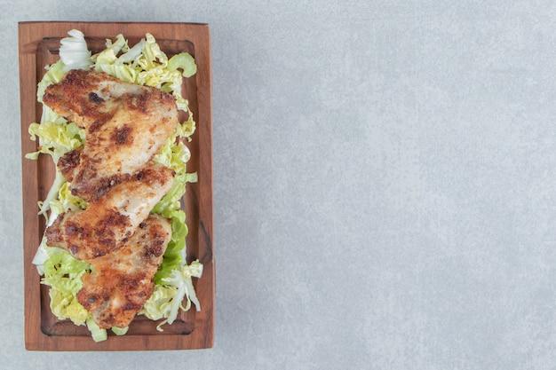 Een houten plank van gebakken kip met sla.