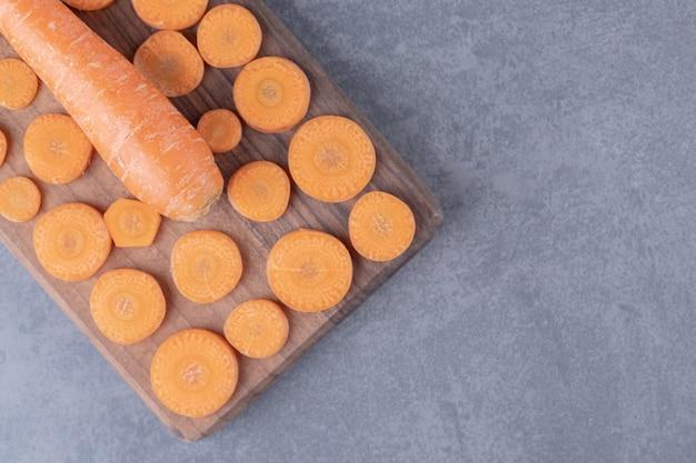 Een houten plank van gesneden en hele wortelen, op het marmeren oppervlak.
