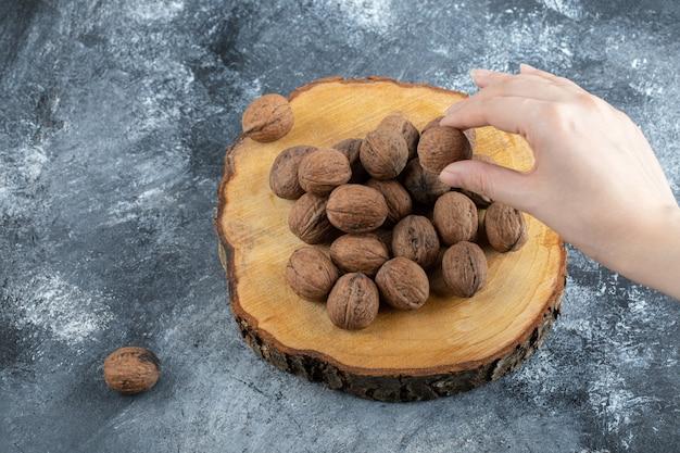 Een houten plank van gezonde walnoten op een grijze ondergrond.
