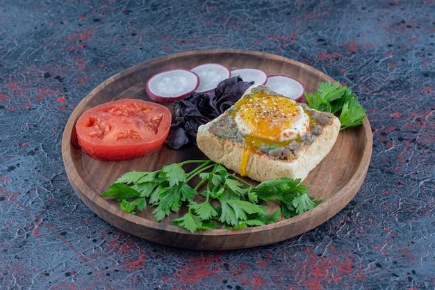 Een houten plank van heerlijke toast met vlees en groenten.