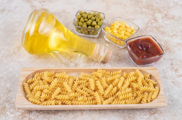 Een houten plank van rauwe spiraalvormige macaroni en een glazen fles olie