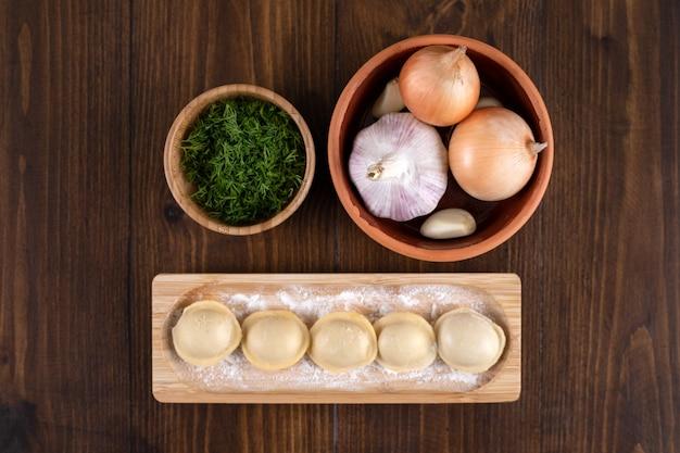 Een houten plank van zelfgemaakte pelmeni-dumplings met een aarden kom uien.