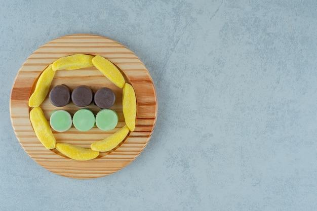 Een houten plank vol met banaanvormige kauwsnoepjes en gelei-snoepjes