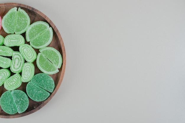 Een houten plank vol met groene, suikerachtige marmelades.