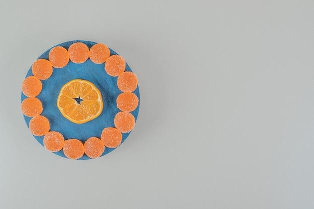 Een houten plank vol met zoete geleisuikergoed en een schijfje sinaasappel.