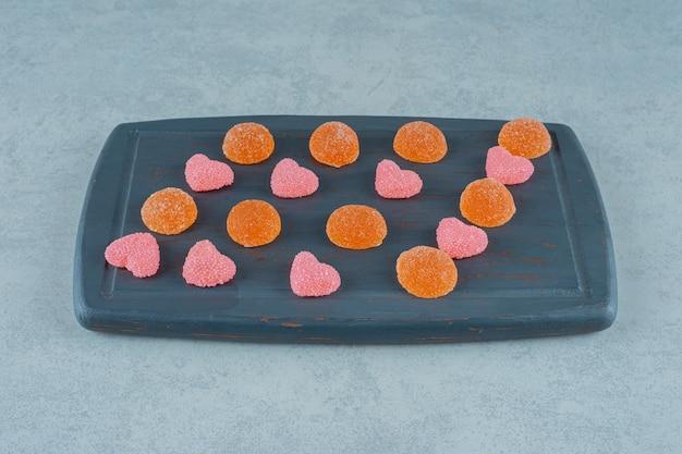 Een houten plank vol oranje suikerachtige gelei-snoepjes met hartvormige gelei-snoepjes