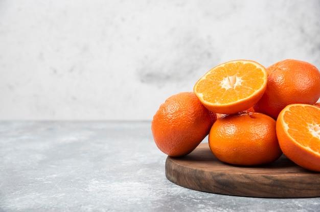 Een houten plank vol sappig oranje fruit met plakjes op stenen tafel.