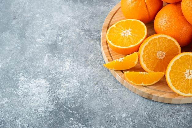 Een houten plank vol sappige plakjes oranje fruit op stenen tafel.