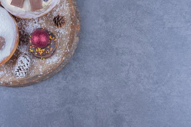 Een houten plank vol taarten met suikerpoeder