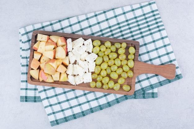 Een houten plank vol witte kaas en gesneden fruit. hoge kwaliteit foto