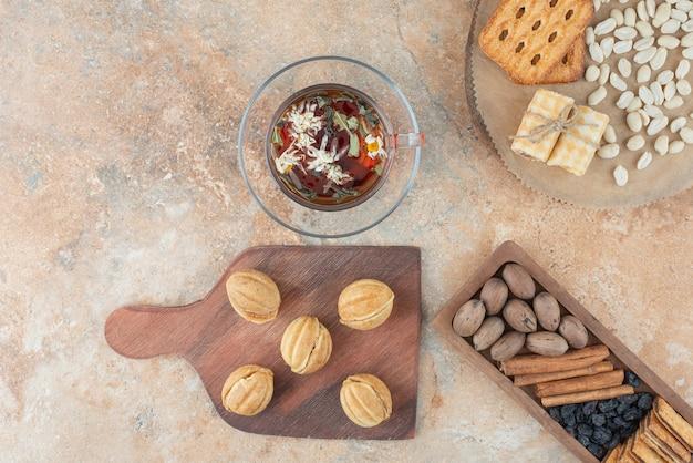 Een houten plank vol zoete koekjes en een kopje kruidenthee