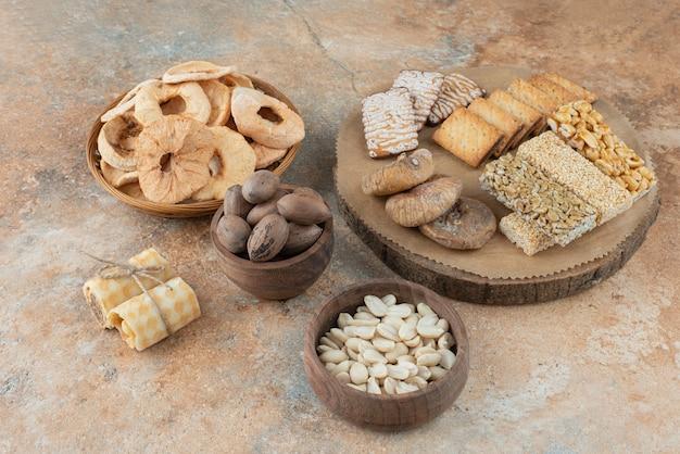 Een houten plank vol zoete koekjes op marmeren achtergrond