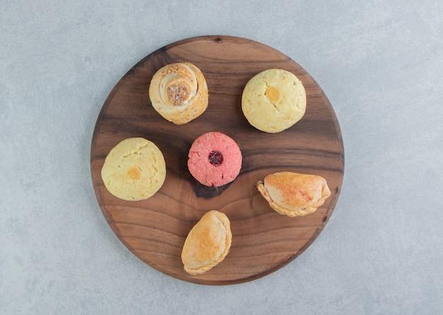 Een houten plank vol zoete koekjes.