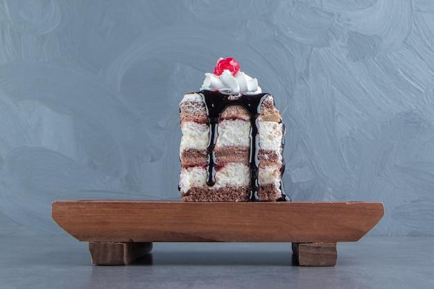 Een houten plankje van een stuk romige cake