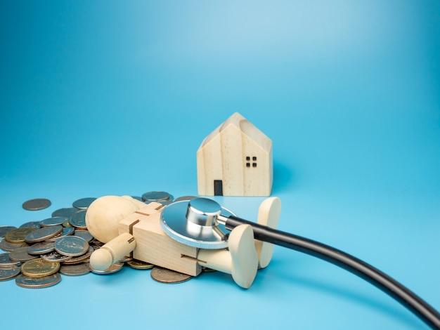 Een houten pop die op stapel geld met een stethoscoop op blauw ligt
