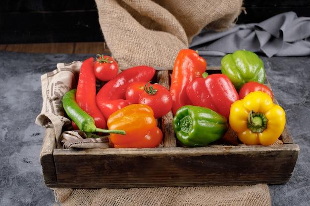 Een houten rustieke dienblad met kleur paprika's en tomaten binnen.