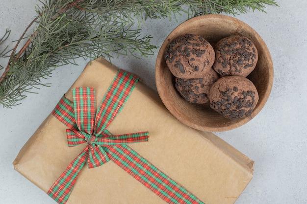 Een houten schaal met chocoladekoekjes met kerstcadeau