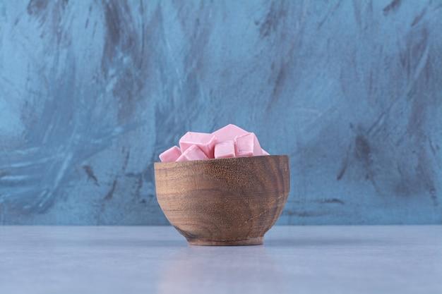 Een houten schaal vol roze zoete zoetwaren pastila.
