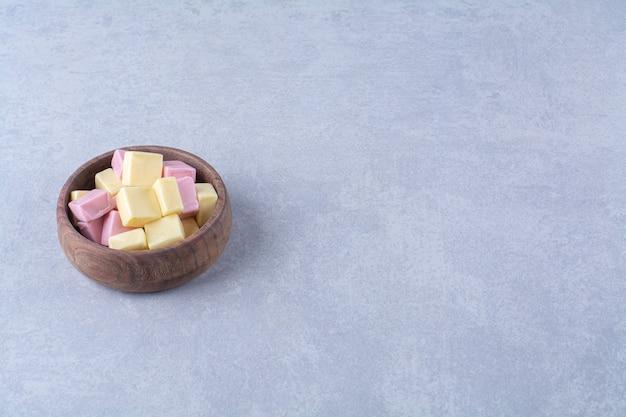 Een houten schaal vol roze zoete zoetwaren
