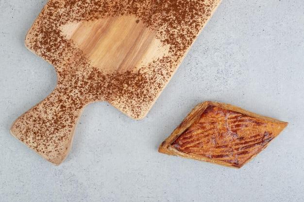 Een houten snijplank met cacaopoeder en koekje.