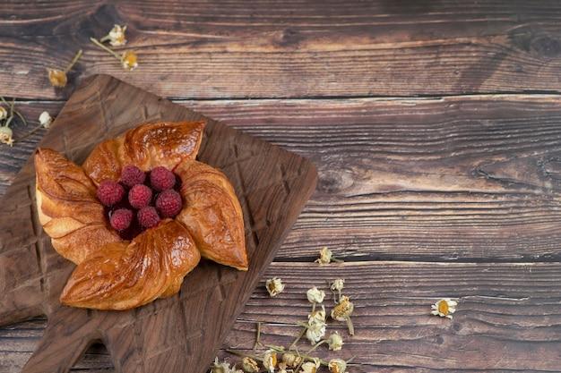 Een houten snijplank met een plakje taart op een houten tafel.