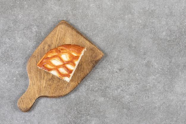 Een houten snijplank met een stukje zoete taart op een stenen ondergrond.