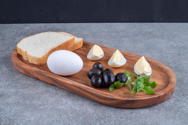 Een houten snijplank met gekookt ei en sneetjes brood. hoge kwaliteit foto
