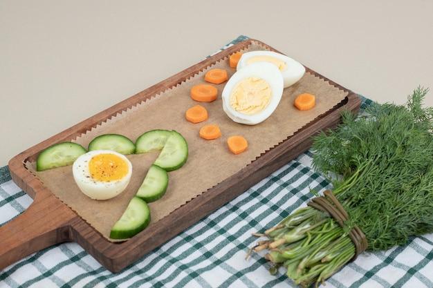 Een houten snijplank met gesneden komkommer en gekookt ei.