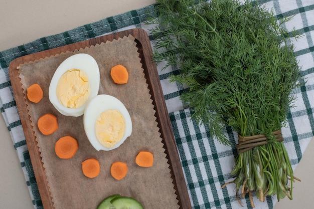 Een houten snijplank met gesneden wortel en gekookt ei.