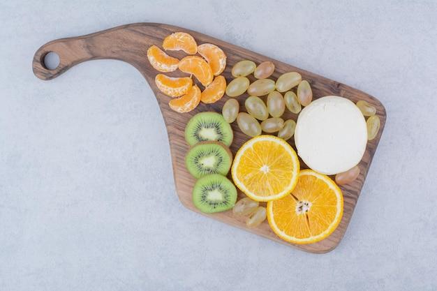Een houten snijplank met hele kaas en gesneden fruit.