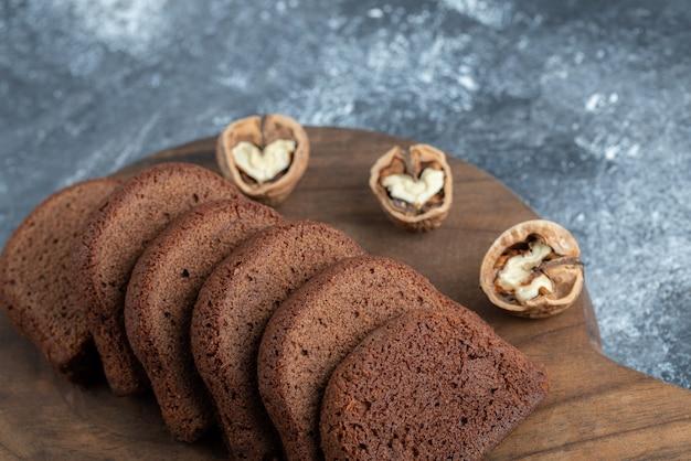 Een houten snijplank met sneetjes brood en walnoten.