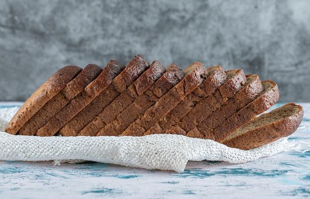 Een houten snijplank met sneetjes brood.